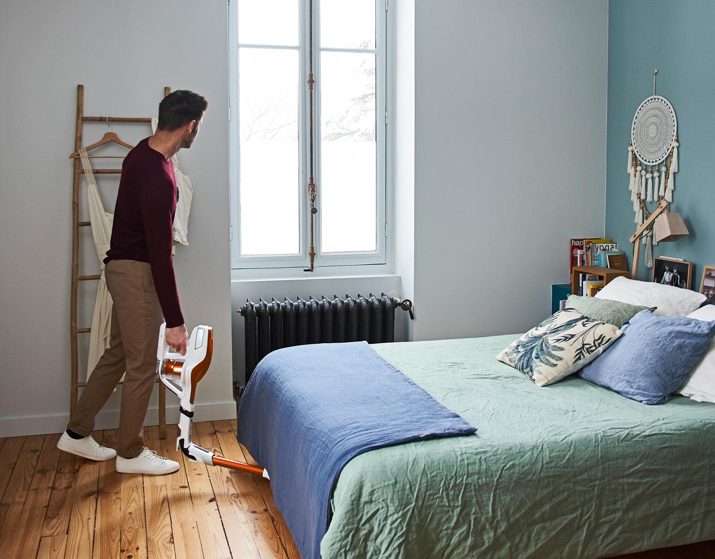 Man stofzuigt onder een bed