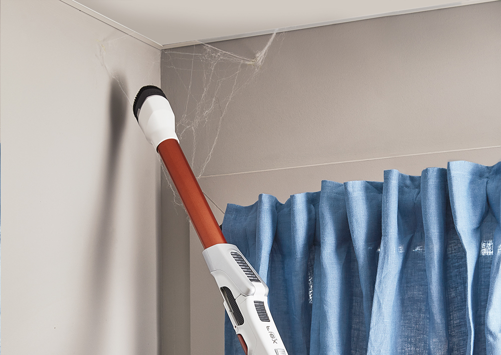 Man stofzuigt de hoek van de kamer
