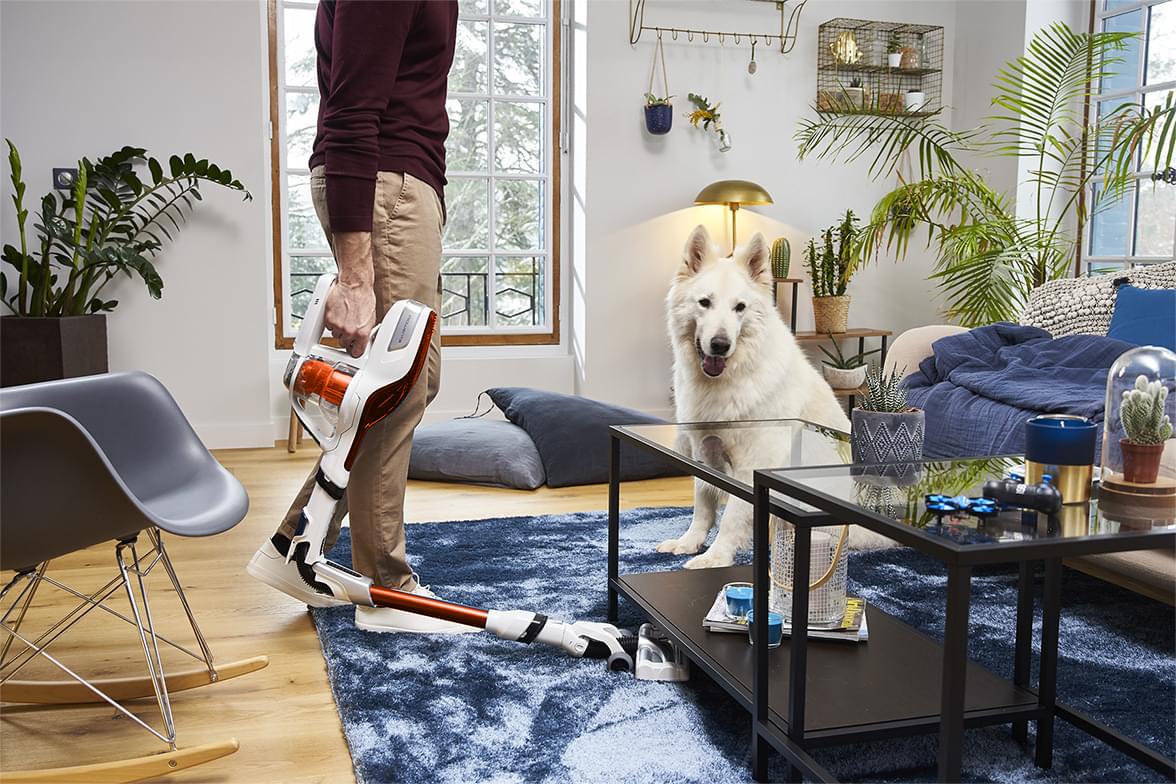 Man stofzuigt terwijl zijn hond toekijkt